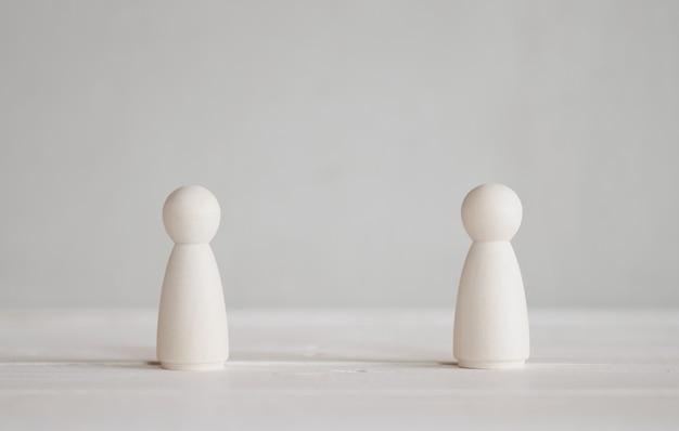 2 bonecos de madeira em pé em cima da mesa