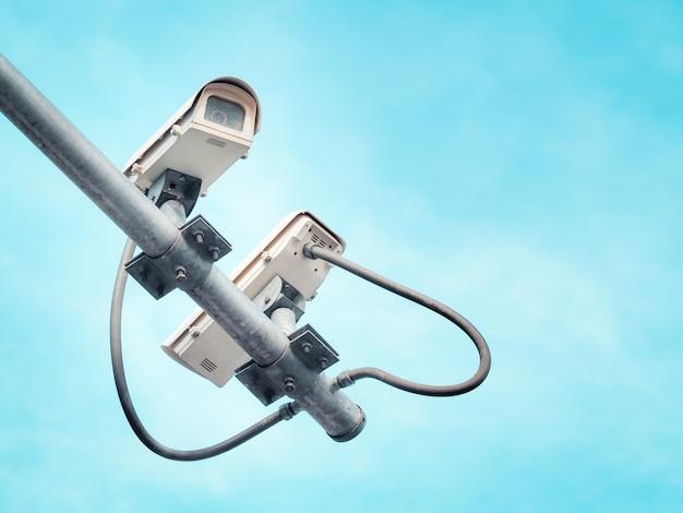 2 câmeras de segurança cctv em um poste alto para proteção pública.