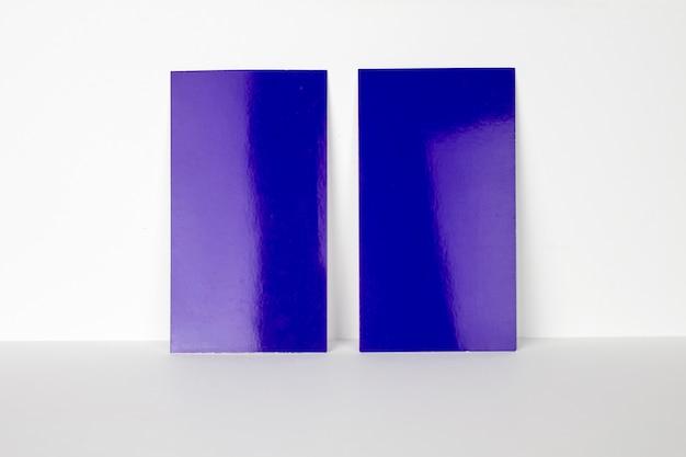 2 cartões de visita azuis em branco trancados na parede branca, tamanho de 3,5 x 2 polegadas