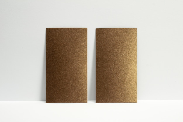 2 cartões de visita de bronze em branco trancados na parede branca, tamanho de 3,5 x 2 polegadas