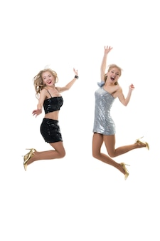2 lindas garotas felizes estão saltando sobre um branco isolado. a alegria de fazer compras. salto congelante, o vôo das meninas.