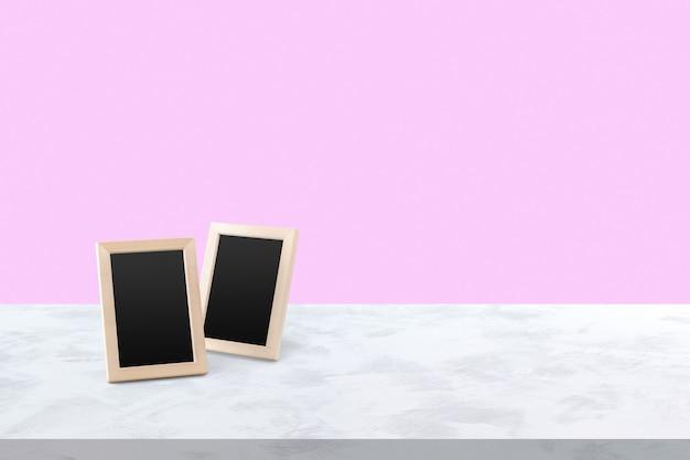 2 molduras brancas em branco sobre a mesa de madeira