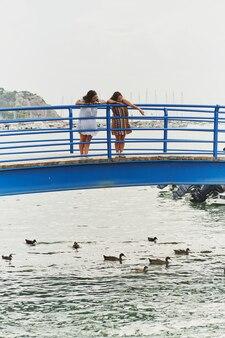 2 mulheres espanholas procurando patos em uma ponte em port d'andratx