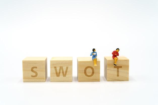 2 pessoas em miniatura sentadas na palavra de madeira swot usando como plano de fundo