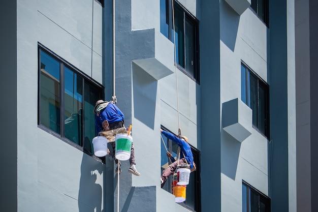 2 pintores estão pendurados em cordas.