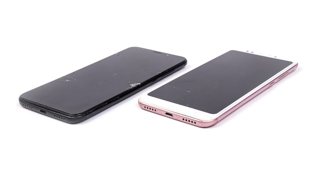 2 telefones quebrados isolados em um fundo branco.