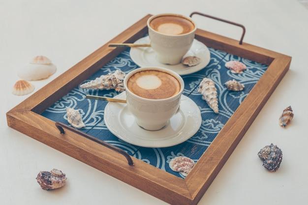 2 xícaras de café na bandeja de servir com itens decorativos em branco.