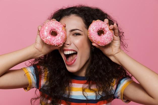 20 anos mulher com cabelo encaracolado se divertindo e segurando rosquinhas isoladas em rosa