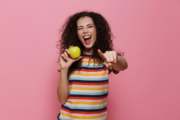 20 anos mulher com cabelo encaracolado sorrindo e segurando uma maçã verde isolada na rosa