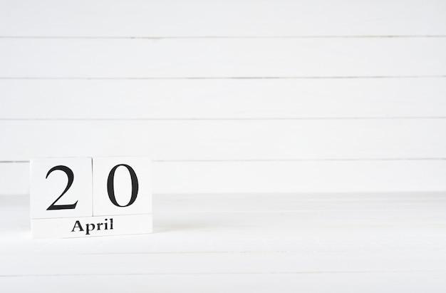 20 de abril, dia 20 do mês, aniversário, aniversário, calendário de bloco de madeira no fundo de madeira branco com espaço da cópia para o texto.