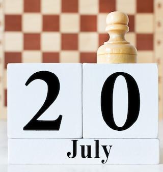 20 de julho - dia internacional do conceito de xadrez. peão no calendário branco com a data de 20 de julho.