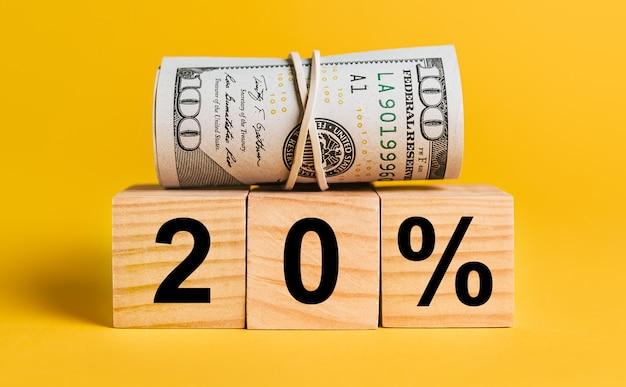20 juros com dinheiro em um fundo amarelo.