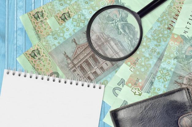 20 notas de hryvnias ucranianas e lupa com bolsa preta e bloco de notas