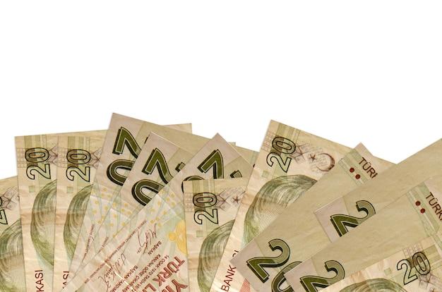 20 notas de liras turcas encontram-se na parte inferior da tela, isolada na parede branca com espaço de cópia.
