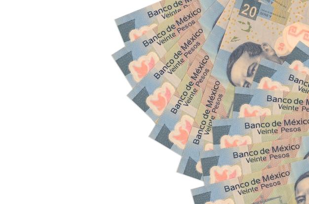 20 notas de pesos mexicanos encontram-se isoladas no fundo branco com espaço de cópia