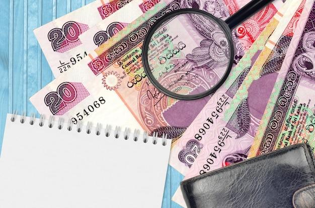 20 notas de rúpias do sri lanka e lupa com bolsa preta e bloco de notas