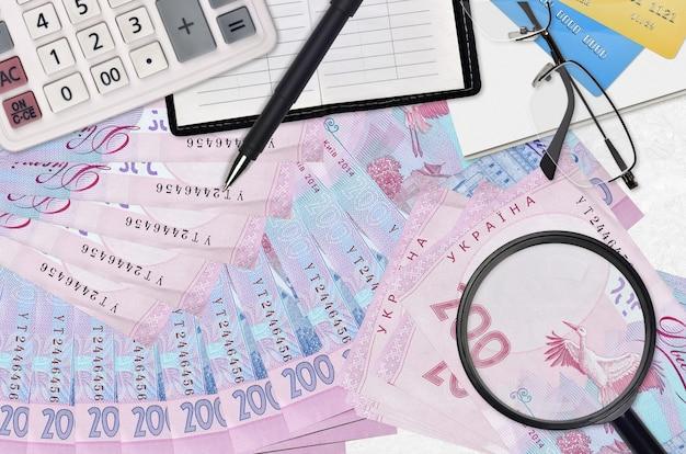 200 contas de hryvnias ucranianas e calculadora com óculos e caneta