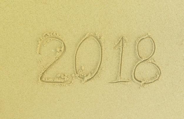 2018 escreva na areia na praia no dia. feliz ano velho.