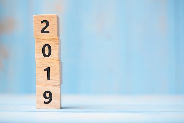 2019 cubos de madeira de ano novo no fundo da tabela azul com espaço de cópia para o texto