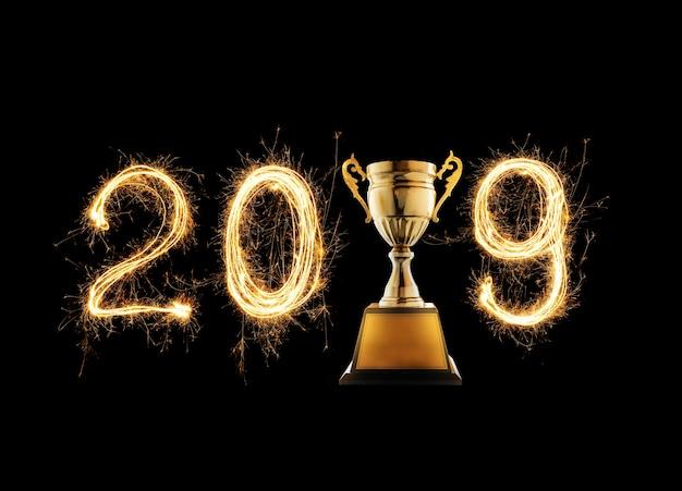 2019 escrito com fogo de artifício da faísca com o troféu dourado do campeão no fundo preto.