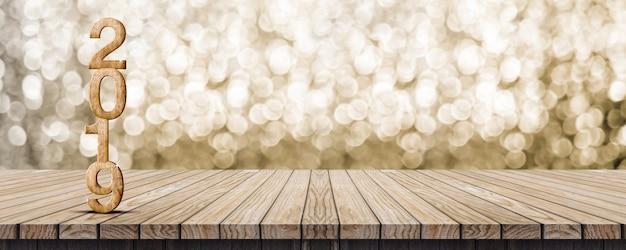 2019 feliz ano novo na mesa de madeira com parede de bokeh ouro cintilante