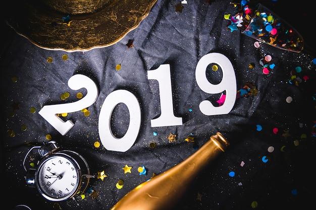 2019 inscrição com relógio e garrafa na mesa