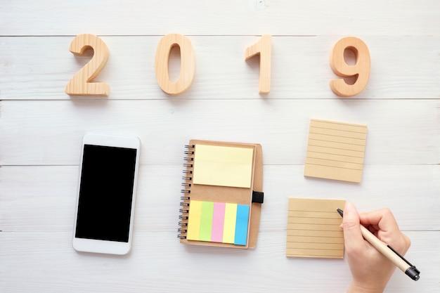 2019 letras de madeira, mão segurando a caneta sobre papel de nota em branco, telefone inteligente em fundo de madeira