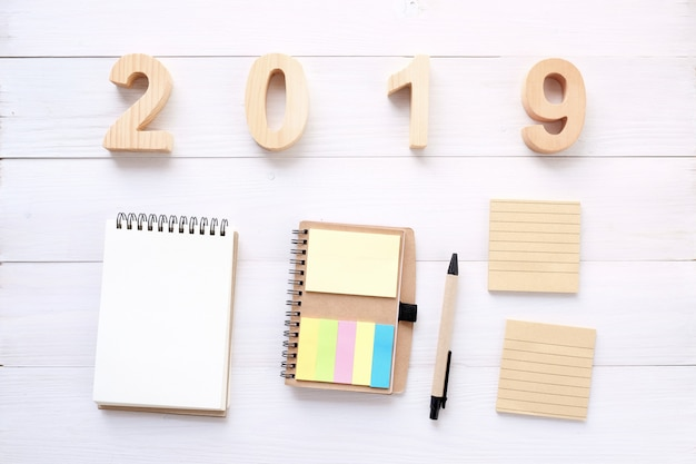 2019 letras de madeira, papel de caderno em branco sobre fundo branco de mesa, com espaço de cópia