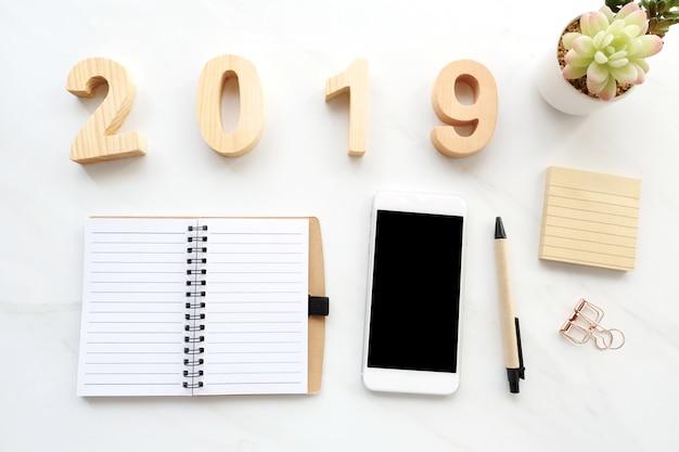 2019 letras de madeira, papel de caderno em branco, telefone inteligente branco com tela em branco