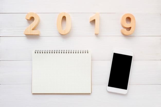 2019 letras de madeira, papel de caderno em branco, telefone inteligente com tela em branco