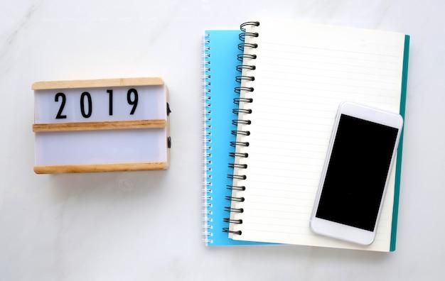 2019 na caixa de madeira, papel de caderno em branco e telefone inteligente com tela em branco