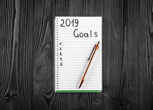 2019 objetivos em seu caderno. conceito de resoluções de ano novo. vista do topo.