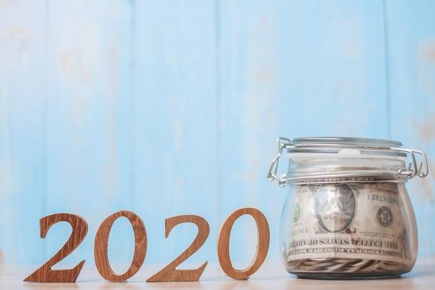 2020 ano novo com frasco de vidro de dinheiro e número de madeira.
