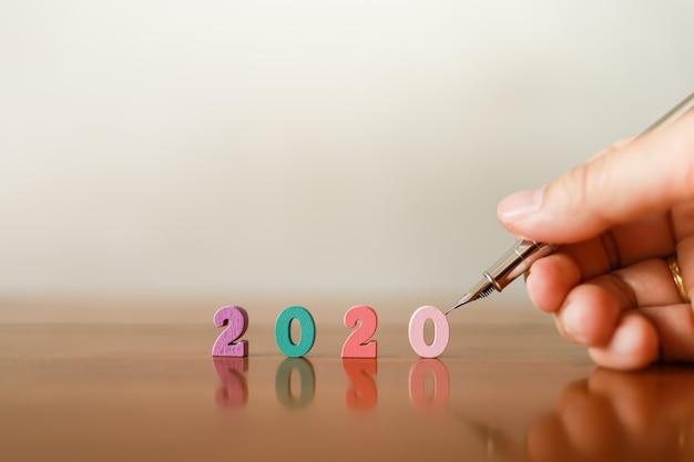 2020 ano novo e o conceito de planejamento. close up da mão do homem que guarda a pena de prata com número de madeira colorido na tabela de madeira com espaço da cópia.