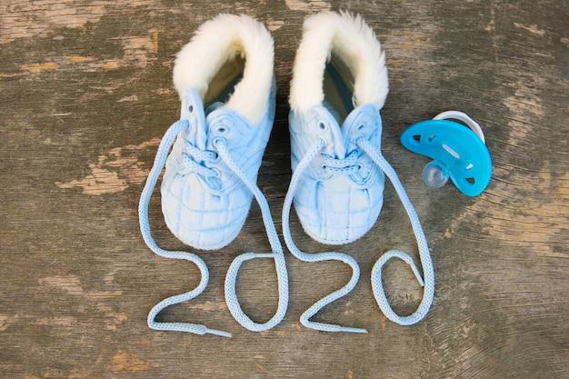 2020 ano novo escrito cadarços de sapatos infantis e chupeta. vista do topo. postura plana.