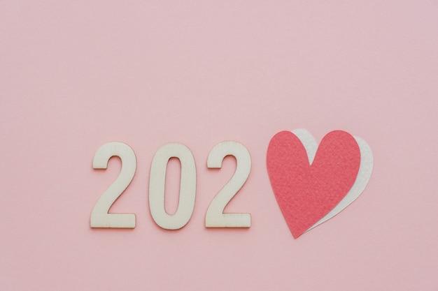 2020 com coração vermelho em fundo rosa pastel