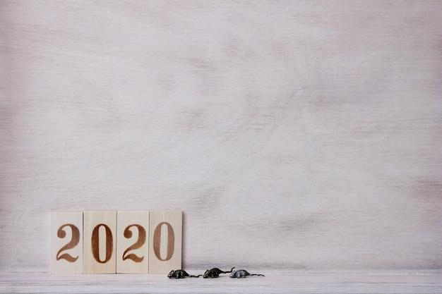 2020 com figuras de madeira na superfície de madeira e um ratinho de metal