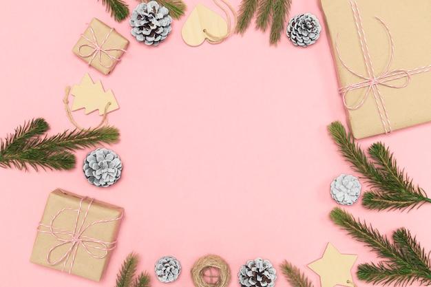 2020 composição do ano novo. conceito de decoração elegante, brinquedo de madeira de natal, caixa de presente de papel kraft, ramos de cones de abeto na rosa