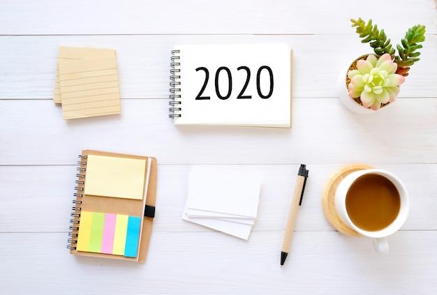 2020 em papel de caderno e em branco organizador de bloco de notas businesscard café lápis sobre fundo madeira