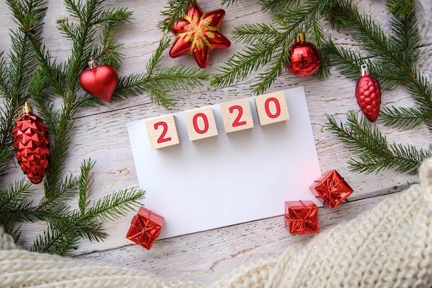 2020 em um quadro de galhos de árvores de natal e brinquedos vermelhos em um fundo de madeira