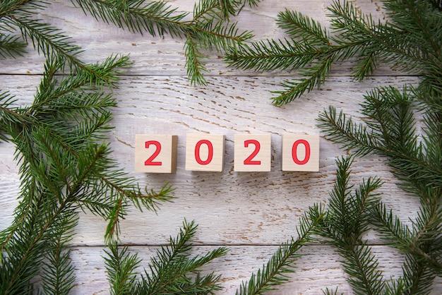 2020 em um quadro de galhos de árvores de natal em um fundo de madeira