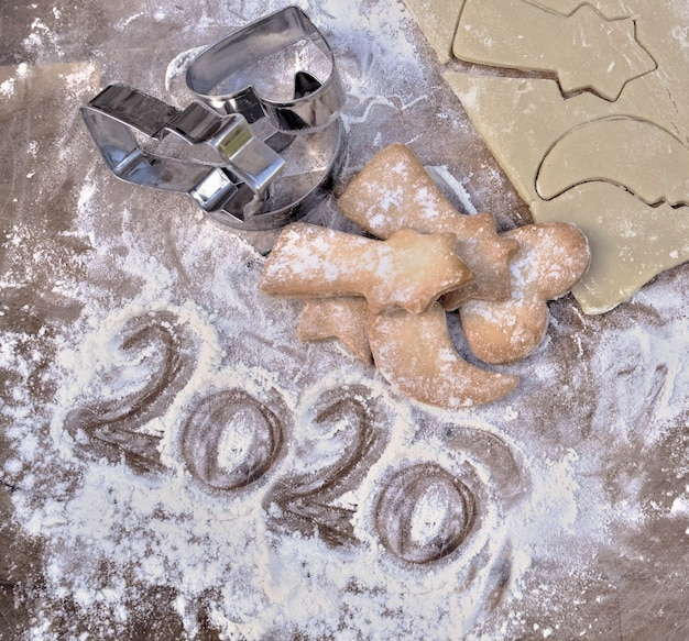 2020 escrito em farinha em uma prancha com biscoitos caseiros