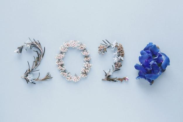 2020 feito de folhas e flores naturais em fundo rosa