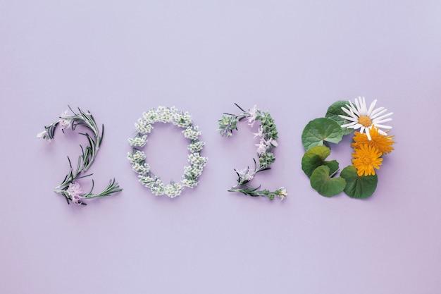 2020 feito de folhas e flores naturais em fundo roxo