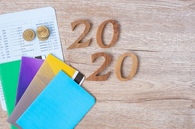 2020 feliz ano novo com banco de livro e moedas na mesa de madeira