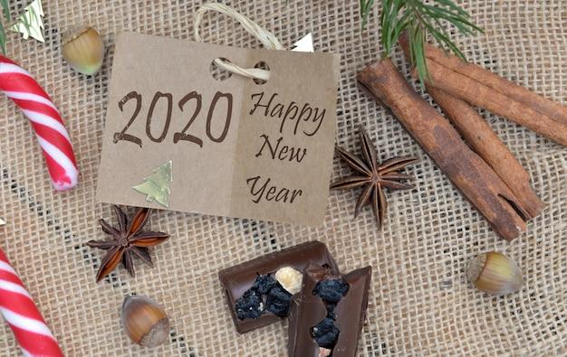 2020 feliz ano novo, escrevendo em um papelão com especiarias e alimentos na decoração de natal