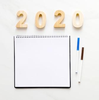 2020 letras de madeira e papel de caderno em branco com espaço de cópia para o conceito de banner de fundo de ano novo de texto