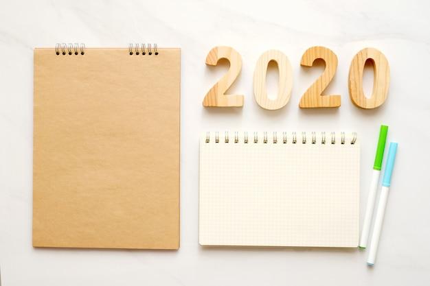 2020 letras de madeira e papel de caderno em branco sobre fundo de mesa de mármore branco