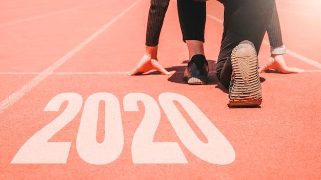 2020 newyear, atleta mulher começando na fila para começar a correr com o número 2020