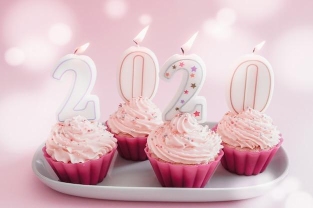 2020 velas em cupcakes com cobertura de creme de chantilly usando copos reutilizáveis de silicone rosa